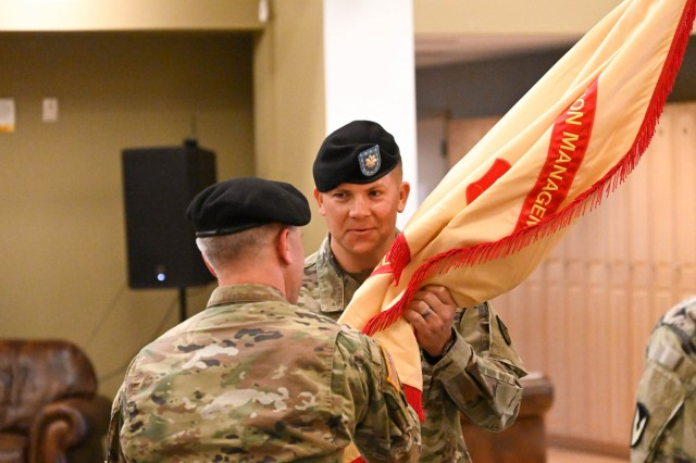Incoming U.S. Army Garrison Alaska, Fort Greely Commander Lt. Col. Joey Orr receives the garrison colors from U.S. Army Garrison Alaska Commander Col. Christopher Ruga during the change of command ceremony June 24 at the Aurora Community Activity Center. The passing of the colors is a time-honored tradition that represents the transfer of authority from the outgoing commander to the incoming commander.