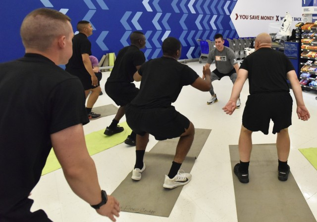 Roy Montez, AAFES BE FIT ambassador, leads motor transport operator trainees assigned to the 58th Transportation Battalion in a 20-minute workout June 26 at the Exchange. Montez, a personal trainer, regularly livestreams workouts on the Exchange Facebook page. The visit here was the first in-person BE FIT workout Montez eventually hopes to take to other installations.