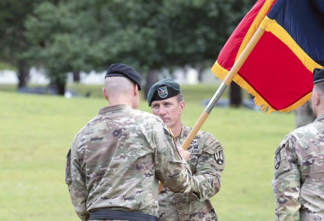 Col. Kent G. Solheim, 165th Infantry Brigade commander, receives the unit colors from Fort Jackson Commander Brig. Gen. Patrick R. Michaelis during a change of command ceremony June 29 at VIctory Field. Solheim took charge of the unit from Col. Eric Flesch.