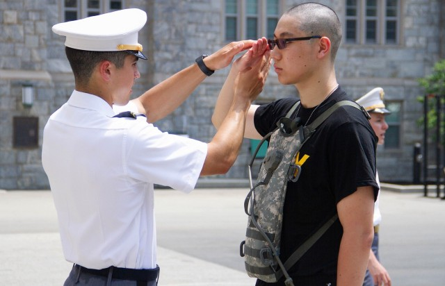 A U.S. Military Academy at West Point junior teaches a new cadet how to salute during Reception Day Monday.