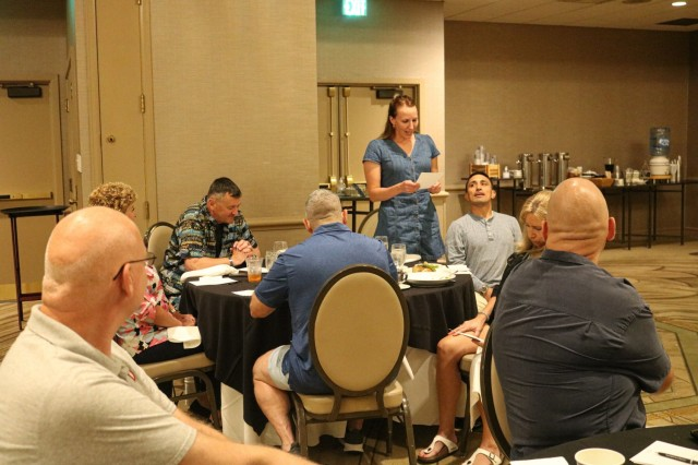 Capt. Marco Lara, commander, Headquarters and Headquarters Company, 1st Theater Sustainment Command, listens along with fellow senior leaders, as his wife Kimberly Pinske-Lara reads what he wrote to introduce her, after being told by the events host that each couple would exchange notepads, during a senior leader's Strong Bonds retreat in Indianapolis, Indiana, June 29, 2021. (U.S. Army photo by Staff Sgt. Nahjier Williams, 1st TSC PAO)