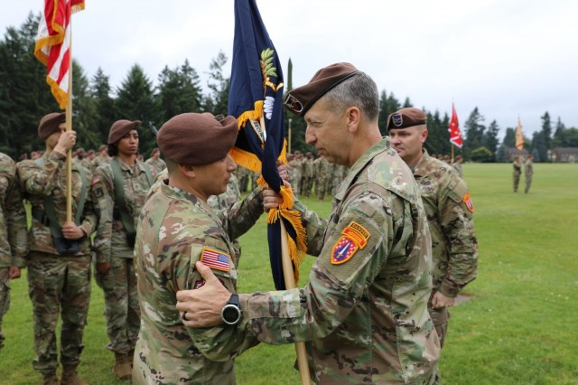 Maj. Gen. Scott Jackson, Commanding General, Security Force Assistance Command, hands the unit colors to Col. Jonathan Chung during the 5th Security Force Assistance Brigade Assumption of Command Ceremony, June 30, 2021 at Joint Base Lewis McChord, Washington.
