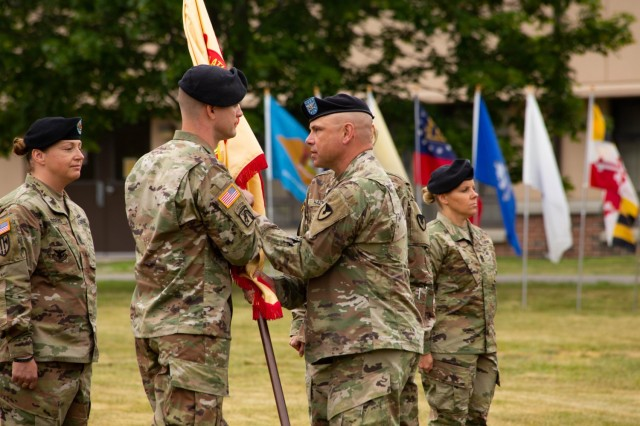 Colonel Jon Brierton from Fort Dix, passes the garrison colors to incoming Garrison Commander Lieutenant Colonel Trent Colestock. Also pictured Garrison Command Sergeant Major Jamie Rogers, and outgoing Garrison Command Sergeant Major Kelli Harr.