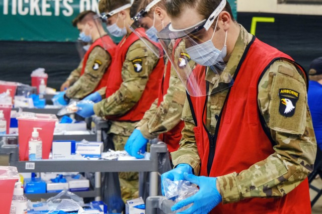U.S. Army Spc. Brandon Hatfield, right, a native of Birmingham, Alabama, and a healthcare specialist from 2nd Brigade Combat Team, 101st Airborne Division (Air Assault), prepares his work station before administering vaccines to local community members at the state-run, federally-supported Wolstein Community Vaccination Center in Cleveland, March 22, 2021. Hatfield said that he feels humbled be part of such an important mission. U.S. Northern Command, through U.S. Army North, remains committed to providing continued, flexible Department of Defense support to the Federal Emergency Management Agency as part of the whole-of-government response to COVID-19. (U.S. Army photo by Sgt. Robert O'Steen, 5th Mobile Public Affairs Detachment)