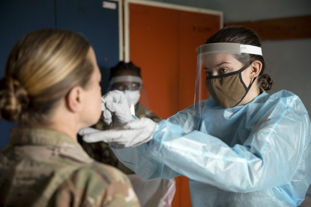 (FARKE AIRFILED, Albania) --- Spc. Elizabeth Porter, a field medic with the 1-131st Aviation Regiment, swabs a soldier's nose for a Covid-19 test, May 16, 2021. Every soldier participating in Defender Europe 21 must take multiple tests to ensure safety for everyone involved in the operation. (Photo by U.S. Army Sgt. Jaccob Hearn)