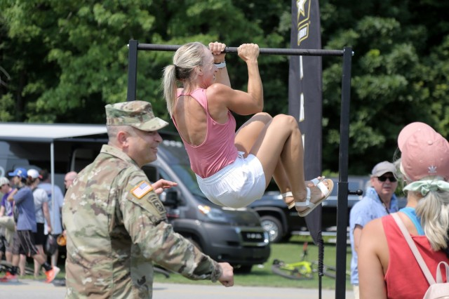 Renee Eckberg, a fitness coach from Oakfield, Wisconsin, performs Army Leg Tucks, one of six events in the U.S. Army's new Army Combat Fitness Test, during the Fourth of July NASCAR Cup Series race at Road America, Elkhart Lake, Wisconsin, July 4, 2021. The U.S. Army recruiting battalion, along with the Appleton Recruiting Company brought recruiters and displays from across their area to meet with citizens, allow them to experience Army technology and evaluate opportunities in military service. Brig. Gen. Ernest Litynski, Commanding General, 85th U.S. Army Reserve Support Command, attended the race as the Army's senior leader and swore in 20 future Soldiers at the pre-race ceremonies. (U.S. Army Reserve photo by Anthony L. Taylor)