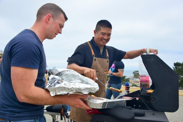 Sgt. 1st Class Solomon Chan, right, assigned to the 229th Military Intelligence Battalion, serves up cheeseburgers during the battalion's Cadre Appreciation Day at Presidio of Monterey, Calif., July 1. Chaplain (Capt.) Jordan Dersch stands left.