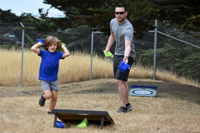 Dylan Farnsworth and his son Nolan, 6, play corn hole during the battalion's Cadre Appreciation Day at Presidio of Monterey, Calif., July 1.
