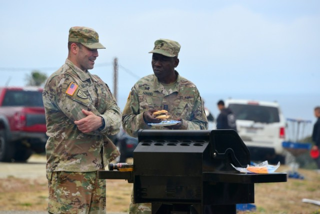 Chaplain (Capt.) Yaw Agbenu, right, and Maj. Steve Gluck talk as they oversee a grill during the 229th Military Intelligence Battalion's Cadre Appreciation Day at Presidio of Monterey, Calif., July 1.