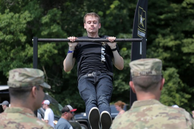 David Williams, from Oak Creek, Wisconsin, performs pull-ups during the Fourth of July NASCAR Cup Series race at Road America, Elkhart Lake, Wisconsin, July 4, 2021. The U.S. Army recruiting battalion, along with the Appleton Recruiting Company brought recruiters and displays from across their area to meet with citizens, allow them to experience Army technology and evaluate opportunities in military service. Brig. Gen. Ernest Litynski, Commanding General, 85th U.S. Army Reserve Support Command, attended the race as the Army's senior leader and swore in 20 future Soldiers at the pre-race ceremonies. (U.S. Army Reserve photo by Anthony L. Taylor)