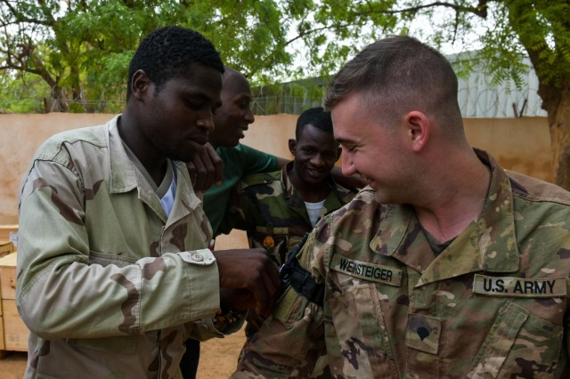 U.S. Army Spc. Andrew Weinsteiger assigned to Headquarters and Headquarters Company, 1st Battalion, 102nd Infantry, 86th Infantry Brigade Combat Team, in support of the Combined Joint Task Force-Horn of Africa (CJTF-HOA) helps out a combat lifesaver class to Nigerien soldiers at Tondibiah, Niger, June 07, 2021. The CLS course is intended to bridge the gap between the minimally-trained average soldier and the highly trained Combat Medic.
