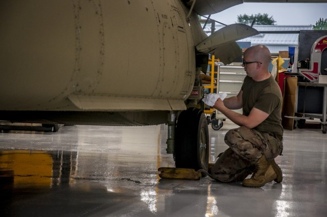 U.S. Army Cpl. Nathaniel Rice, a CH-47 Chinook Mechanic, performs maintenance on the aft landing gear of a helicopter that was battle damaged from a hard landing while serving in Iraq in the maintenance bay of the Connecticut National Guard's 1109th Theater Aviation Support Maintenance Group in Groton, Conn. June 22, 2021. The TASMG recovered this helicopter from Kuwait and performed a complete overhaul of the aircraft in order to get it back into the Army's operational fleet.