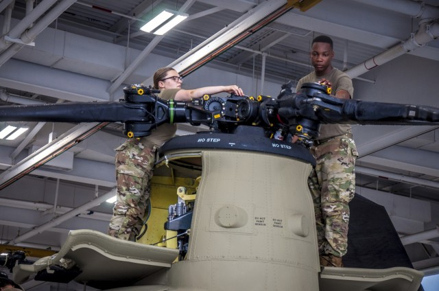 U.S. Army Spc. Kaitlin Cavanaugh and Sgt. Omar Sewell conduct maintenance on the forward rotor of a CH-47 Chinook helicopter that was battle damaged from a hard landing while serving in Iraq in the maintenance bay of the Connecticut National Guard's 1109th Theater Aviation Support Maintenance Group in Groton, Conn. June 22, 2021. The TASMG recovered this helicopter from Kuwait and performed a complete overhaul of the aircraft in order to get it back into the Army's operational fleet.
