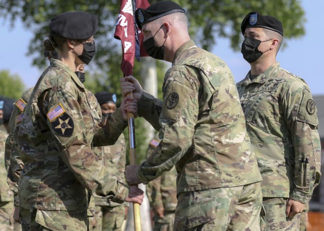 Vicenza, Italy – U.S. Army Lt. Col. Carla Schneider (left) receives the U.S. Army Health Clinic Vicenza colors from U.S. Army Col. Andrew Landers (center), commander of Landstuhl Regional Medical Center, during a change of command ceremony where U.S. Army Lt. Col. Joseph Matthews (right) relinquished command of USAHC-V to Schneider at U.S. Army Garrison Italy, June 22.