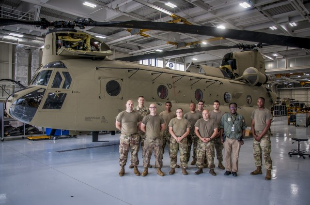 The team responsible for the complete overhaul of a CH-47 Chinook helicopter that was battle damaged from a hard landing while serving in Iraq pose for a group photo in front of the helicopter at the Connecticut National Guard's 1109th Theater Aviation Support Maintenance Group in Groton, Conn. June 22, 2021. The work being done on the aircraft was part of a new initiative from the unit to restore inoperable aircraft and get them back in the Army's operational fleet.