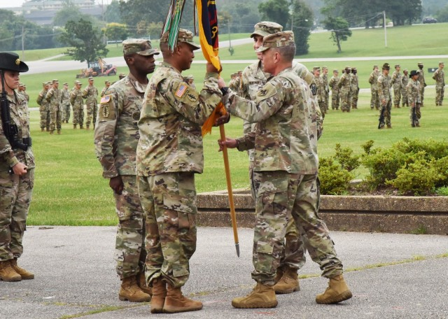 During a change-of-command ceremony July 8 on Gammon Field, Col. Fredrick Parker (center left) accepts the 3rd Chemical Brigade colors from Col. Sean Crockett, U.S. Army Chemical, Biological, Radiological and Nuclear School commandant, as Col. Adam Hilburgh, outgoing commander, and Command Sgt. Maj. Joe Johnson look on.