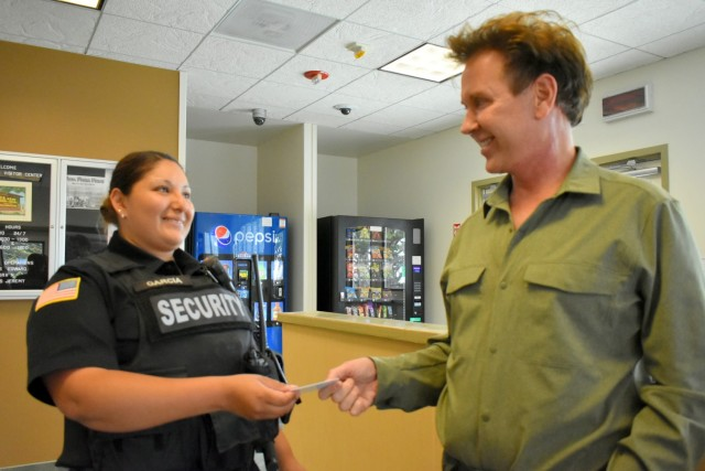 Officer Monica Garcia Gonzalez, left, a security guard at Presidio of Monterey, hands Gwyn De Amaral, a Gold Star survivor, his new Survivor Access Badge at the Visitors Center, PoM, Calif., June 29.