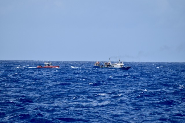 The crew of the Coast Guard Cutter Midgett (WMSL 757) aboard a small boat approaches a fishing vessel to conduct a fisheries law enforcement boarding in the Pacific Ocean on April 14, 2020. Midgett's successful first patrol countering IUU fishing to promote maritime governance in Oceania is essential to U.S. national security and to support Pacific Island Forum countries whose resource security is vital to their own national security. (U.S. Coast Guard photo by USCGC Midgett/Released)