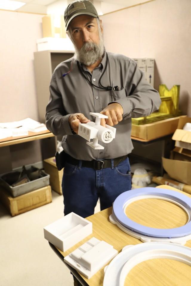 Mark Mireles, Tool Engineer, proudly displays several 3D printed shop aids at Corpus Christi Army Depot