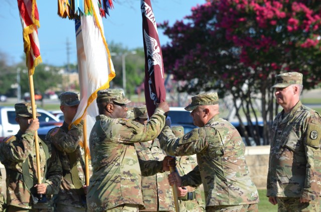 Fort Hood, Texas – Col. Paul Colthirst, commander, U.S. Army Fort Hood Dental Health Activity receives the guidon from Col. Rafael Caraballo, commander, Dental Health Command-Central during a change of command ceremony in which he to command from Col. Stefan Olpinski on Hildner Field July 1.