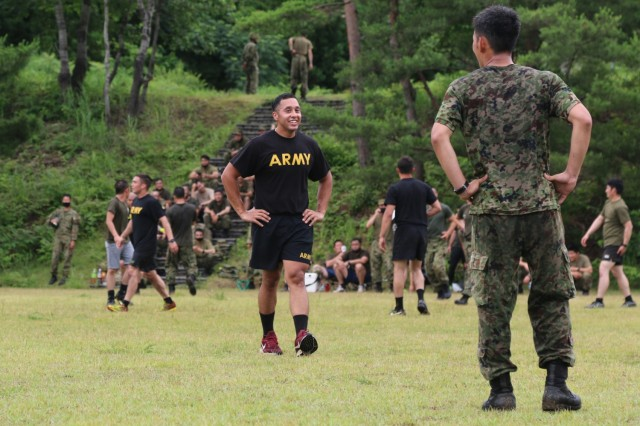 A Soldier assigned to 1st Battalion, 28th Infantry Regiment, 3rd Infantry Division, shares a laugh with a member of the Japan Ground Self-Defense Force during an ultimate Frisbee tournament between Soldiers assigned to 1st Battalion, 28th Infantry Regiment, 3rd Infantry Division, and JGSDF members on Aibano Training Area, Japan, July 2, 2021. Soldiers and members of the JGSDF participated in the tournament in a short break from training during exercise Orient Shield. Orient Shield is the largest U.S. Army and JGSDF bilateral field training exercise being executed in various locations throughout Japan to enhance interoperability and test and refine multi-domain and cross-domain operations.