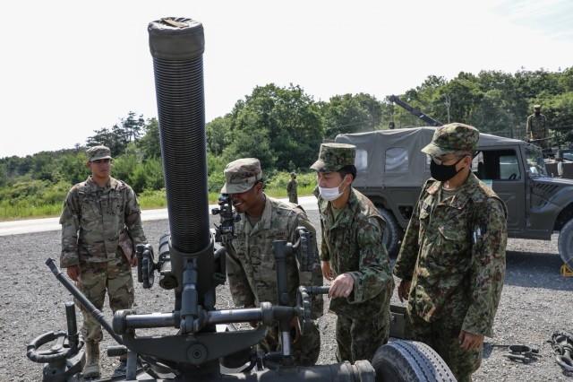 U.S. Army Soldiers assigned to 1st Battalion, 28th Infantry Regiment, 3rd Infantry Division, look through the optics of a Japan Ground Self-Defense Force 120mm mortar as JGSDF members observe during an equipment display on Aibano Training Area, Japan, June 28, 2021, as part of exercise Orient Shield. Orient Shield is the largest U.S. Army and JGSDF bilateral field training exercise being executed in various locations throughout Japan to enhance interoperability and test and refine multi-domain and cross-domain operations.