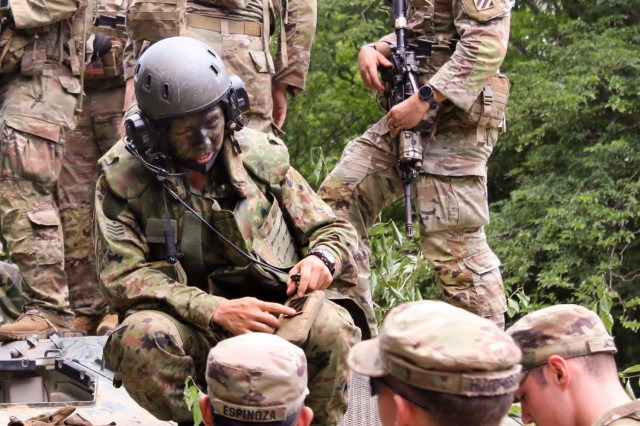 """U.S. Army Soldiers of 1st Battalion, 28th Infantry Regiment """"Black Lions,"""" 3rd Infantry Division, give a 3rd Infantry Division unit patch to a member of Japan Ground Self-Defense Force's 15th Rapid Deployment Regiment June 25, 2021, on Aibano Training Area, Japan, during bilateral training as part of exercise Orient Shield 21-2. Exercise Orient Shield marks a continued commitment by the United States and Japan to work as dedicated partners in support of the Japan-U.S. security alliance and for peace and stability in the Indo-Pacific region."""