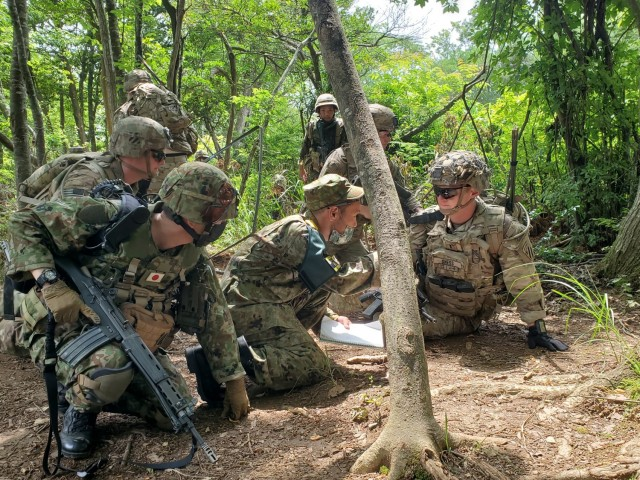 """U.S. Army 1st Lt. Tyler Gness, a mortar platoon leader with 1st Battalion, 28th Infantry Regiment """"Black Lions,"""" 3rd Infantry Division, speaks through a translator to his counterparts from the Japan Ground Self-Defense Force during mortar training at Aibano Training Area, Japan, June 30, 2021. Orient Shield is the largest U.S. Army and JGSDF bilateral field training exercise being executed at various locations throughout Japan to enhance interoperability and test and refine multi-domain and cross-domain operations."""
