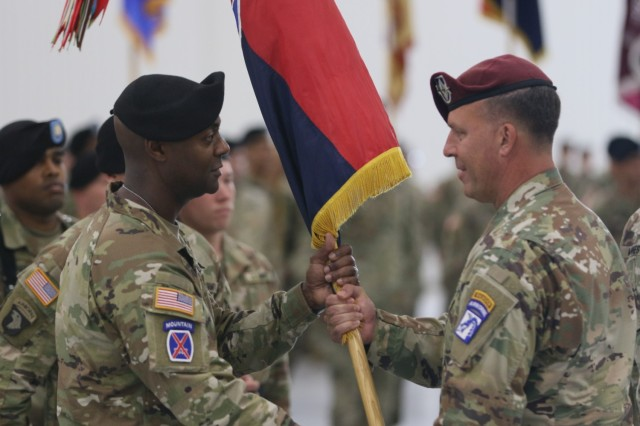 Lt. Gen. Michael E. Kurilla, XVIII Airborne Corps commander (right), passes the 10th Mountain Division (LI) colors to Brig. Gen. Milford Beagle Jr., during the division change of command ceremony July 12 at Wheeler-Sack Army Airfield. (Photo by Sgt. Brandon Cox, 10th Mountain Sustainment Brigade Public Affairs)