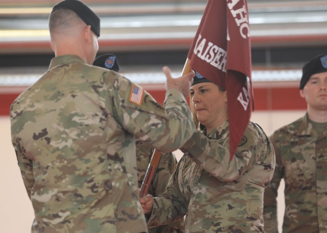 U.S. Army Maj. Shara Fisher transfers the U.S. Army Health Clinic Kaiserslautern unit colors to U.S. Army Col. Andrew Landers, commander, Landstuhl Regional Medical Center, during a change of command ceremony where Fisher relinquished command to U.S. Army Maj. Stephen Harmon at Kleber Kaserne, June 30.