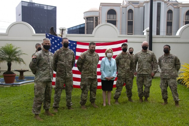 Soldiers assigned to 75th Troop Command, Kentucky National Guard, and the U.S. Ambassador to Guyana Sarah Ann Lynch (center), pose for a photo, after completing their Oath of Renlistment, given by Lt. Col. Timothy Stark, commander, 75th TC (left), during Tradewinds 21, at the U.S. Embassy in Guyana, June 22, 2021. Tradewinds 21 is a U.S. Southern Command (SOUTHCOM) sponsored Caribbean security-focused exercise in the ground, air, sea, and cyber domains; working with partner nations to conduct joint, combined, and interagency training, focused on increasing regional cooperation and stability.