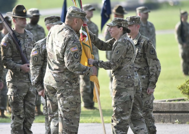 Brig. Gen. Niave Knell, U.S. Army Military Police School commandant, passes the 14th Military Police Brigade colors to Col. Kirk Whittenberger during a change-of-command ceremony July 14 on Gammon Field.