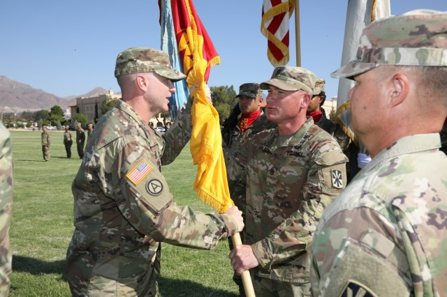 Col. Timothy L. Woodruff, incoming brigade commander, 11th Air Defense Artillery Brigade, 32d Army Air and Missile Defense Command, hands off the Brigade guidon to Command Sgt. Maj. Robert Walker during the change of command ceremony. Col. John L. Dawber, outgoing commander, 11th ADA BDE, relinquished command to Woodruff, July 9, 2021, on Noel Parade Field, Fort Bliss, Texas.