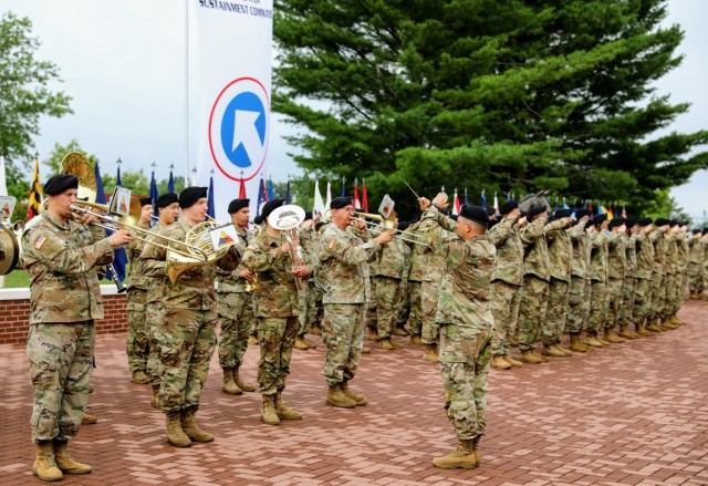 The 1st Armored Division Band, conducted by Stephen Schultz, plays the national anthem during the change of command ceremony between Maj. Gen. John P. Sullivan, outgoing commanding general, 1st Theater Sustainment Command, and Maj. Gen. Michel M. Russell, Sr., incoming commanding general, 1st TSC, July 13, 2021 outside of Fowler Hall at Fort Knox, Kentucky.
