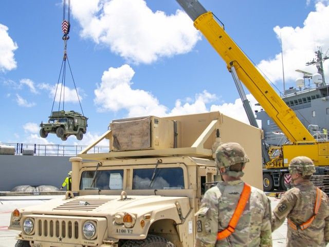 Soldiers from 593rd Expeditionary Sustainment Command observe a HMMWV being lifted from an Army Watercraft System in support of Forager 21, Naval Base Guam, July 10, 2021. Army Watercraft Systems deliver sealift capabilities that increase the Theater Army's freedom of action and ability to flow forces to and within the region (U.S. Army photo by Spc. Richard Carlisi, I Corps Public Affairs)