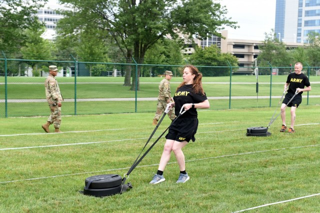 Staff Sgt. Alyssa N. Fowler, center, Human Resources Non-commissioned Officer, 84th Training Division, pulls a 90-pound sled during the Sprint-Drag-Carry portion of the Army Combat Fitness Test. The 85th USARSC conducted a diagnostic ACFT at its headquarters in Arlington Heights, Illinois July 10-11, 2021. The U.S. Army expects to fully implement the ACFT in 2022, replacing the 40-year old Army Physical Fitness Test.    (U.S. Army Reserve photo by SSG Erika F. Whitaker)
