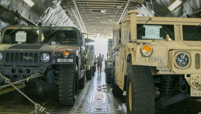 A fleet of military vehicles are loaded onto a C-5 Galaxy for exercise Forager 21, at Joint Base Lewis-McChord, Wash., July 8, 2021. This exercise allows both the Army and Air Force  stationed at JBLM to practice their ability to rapidly deploy forces to the Pacific.