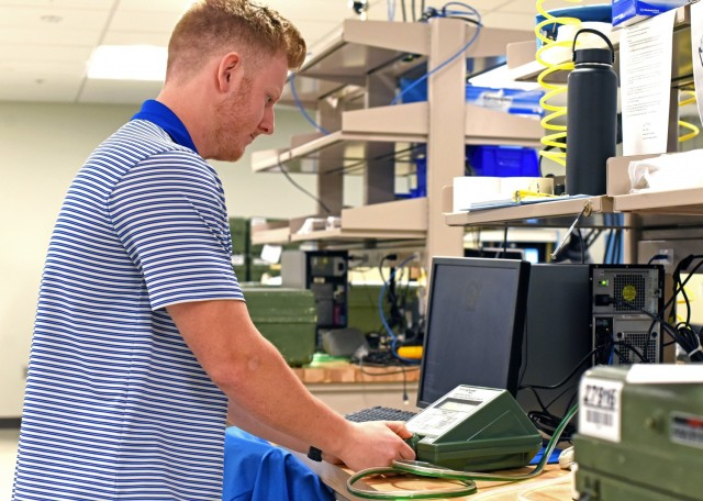 """Caleb Baker, an engineering intern from the University of Alabama in Huntsville, demonstrates an """"as-found"""" test conducted on a gas mask tester in the Protection Assessment Test System laboratory at Redstone Arsenal, Ala., April 28. The PATS lab, which is part of the U.S. Army Test, Measurement, and Diagnostic Equipment Activity, is responsible for ensuring every gas mask in the Department of Defense functions appropriately."""