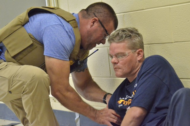 Sergeant Dave Keenom, Montgomery County Sheriff's Office, left, practices applying a tourniquet to Jacob Hayes, a firefighter role-playing as a shooting victim, during Active Attack Integrated Response training, hosted July 12-16 at Jackson Elementary School.