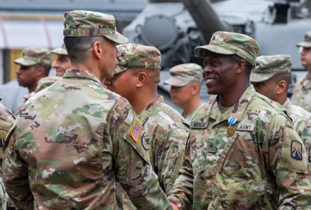 The 16th Sustainment Brigade Commander Col. Angel Estrada shakes the hand of Sgt. Austin McNeal, a wheeled vehicle mechanic with the 53rd Movement Control Battalion, 7th Transportation Battalion (Expeditionary), after he was awarded the Army Achievement Medal in Żagań, Poland, July 14, 2021. Soldiers of the 53rd were awarded medals for their performance in supporting Atlantic Resolve. There are four types of U.S. Army Atlantic Resolve rotations – armored, aviation, sustainment task force, and division forward headquarters. (U.S. Army photo by Pfc. Michael Baumberger/released)
