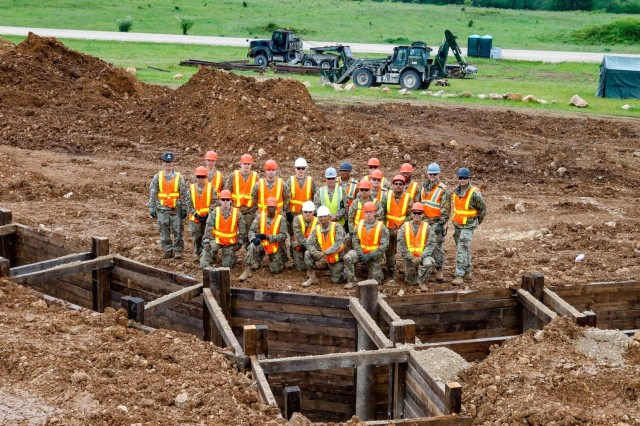 Members of the Joint Multinational Readiness Center's Troop Construction Program and 2nd Cavalry Regiment's Third Platoon, Argonaut Troop, Regimental Engineer Squadron, stand alongside a 100-meter platoon-minus trench June 4 that they had been constructing since May 15 on Hohenfels Training Area, Hohenfels, Germany. The two units worked together to complete the trench, which will be used on HTA for training events for a multitude of units in the upcoming years, beginning with the European Best Sniper Competition August 5 to 14, 2021, at HTA, Germany. (U.S. Army photo by Master Sgt. Ryan C. Matson)