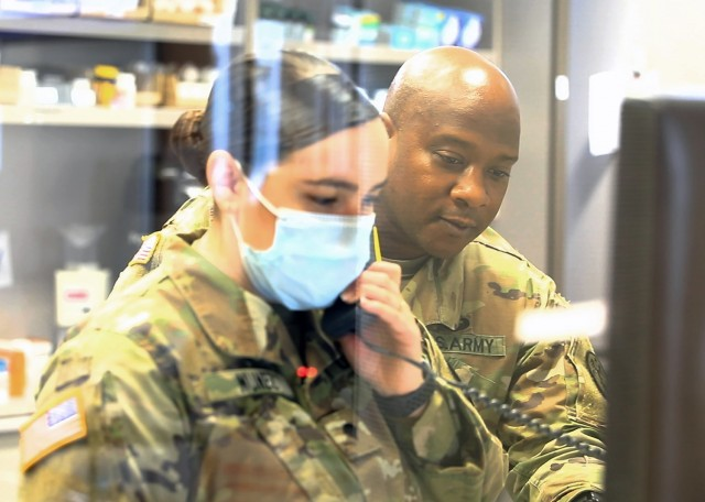 U.S. Army Sgt. Walter Howard II, noncommissioned officer in charge, Pharmacy Department, U.S. Army Health Clinic Baumholder, provides assistance to a junior Soldier at the USAHC Baumholder Pharmacy, May 26.