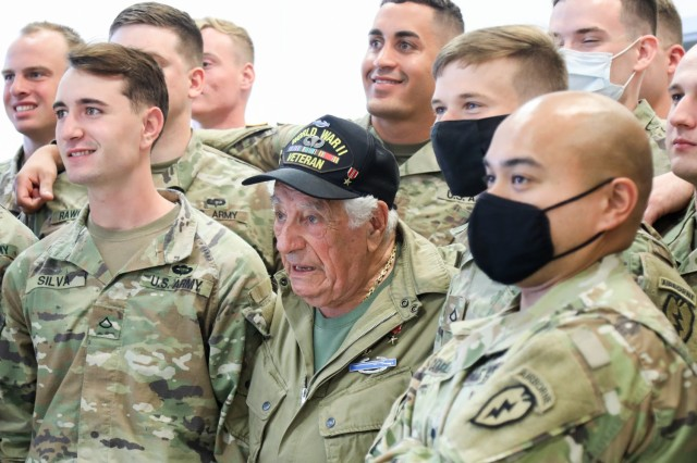 """Vincent Speranza, World War II Veteran and machine gunner from the 501st Infantry Regiment, takes a group photo with junior paratroopers of the 1st Battalion, 501st Infantry Regiment, during a visit to Joint Base Elmendorf-Richardson, July 15, 2021. Speranza traveled to JBER to meet and share stories about his World War II experiences with the paratroopers of the 1-501st PIR and the 4th Infantry Brigade Combat Team (Airborne), 25th Infantry Division, """"Spartan Brigade."""" The Spartan Brigade is the only airborne infantry brigade combat team in the Arctic and Pacific theaters, providing the combatant commander with the unique capability to project an expeditionary force by air."""
