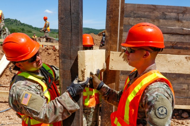 Sgt. Edgar Ortiz, left, a horizontal engineer with third platoon, Argonaut Troop, Regimental Engineering Squadron, 2nd Cavalry Regiment, and Spc. Garrett Easterling, also from third platoon, work on the wooden frame of a 100-meter trench on Hohenfels Training Area, Hohenfels, Germany, June 3, 2021. The trench will be utilized for a number of training events throughout the year, beginning with the European Best Sniper Competition Aug. 5-14 on HTA. (U.S. Army photo by Master Sgt. Ryan C. Matson)