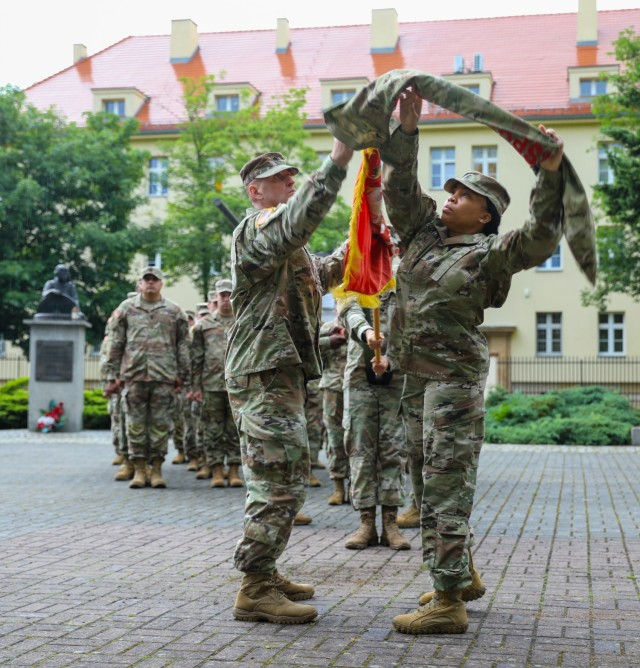 The 49th Transportation Battalion Commander Lt. Col. Andrew Carpenter and Command Sgt. Maj. Tamara Williams uncase their colors during a transfer of authority ceremony in Żagań, Poland, July 14, 2021. Uncasing the colors signifies that the transfer of authority from the 53rd Movement Control Battalion is complete, and that the 49th stands strong and ready to perform its mission in support of Atlantic Resolve. Atlantic Resolve demonstrates continued U.S. commitment to collective European security through a series of actions designed to reassure NATO allies and other European partners of America's dedication to enduring peace and stability throughout Europe. (U.S. Army photo by Staff Sgt. Jennifer Reynolds)