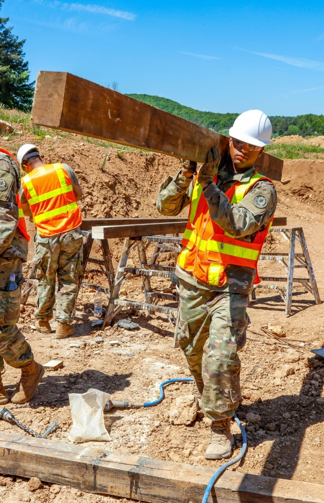 Sgt. Deivy Capellan, a horizontal engineer with third platoon, Argonaut Troop, Regimental Engineering Squadron, 2nd Cavalry Regiment, carries a piece of treated and stained lumber during the construction of a 100-meter trench on Hohenfels Training Area, Hohenfels, Germany, June 3, 2021. The trench will be utilized for a number of training events throughout the year, beginning with the European Best Sniper Competition Aug. 5-14 on HTA. (U.S. Army photo by Master Sgt. Ryan C. Matson)