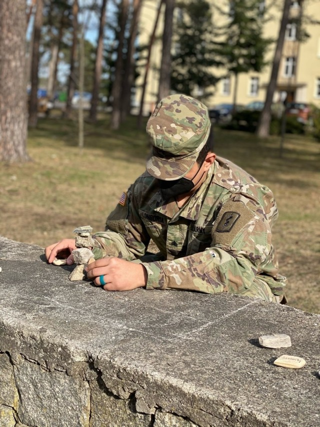 A Soldier demonstrates mindfulness rock stacking activity to RRC participants. U.S. Army photo by Maj. Ashley Welsh.