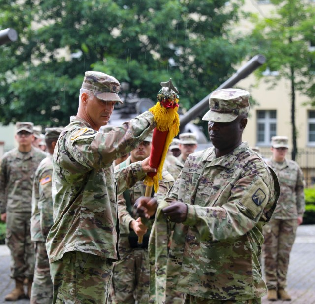 The 53rd Movement Control Battalion Commander Lt. Col. Aaron Cornett and Command Sgt. Maj. LaVaughn Brown case their colors during a transfer of authority ceremony in Żagań, Poland, July 14, 2021. Members of the 53rd completed a nine-month rotation in support of Atlantic Resolve, helping provide ready and postured combat-credible forces through multinational training and security cooperation activities. (U.S. Army photo by Staff Sgt. Jennifer Reynolds)