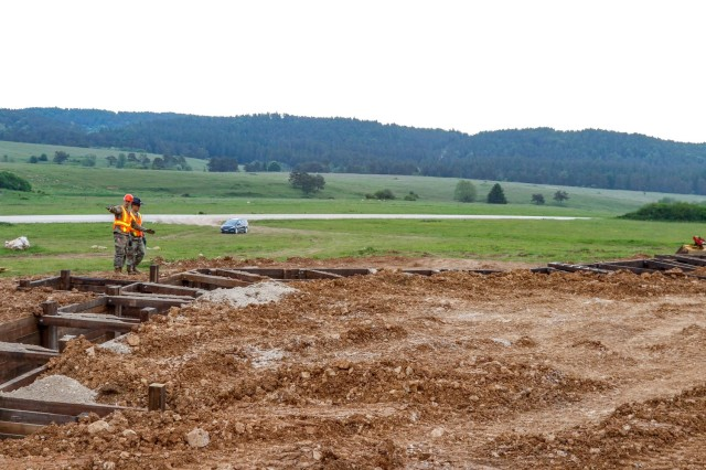 2nd Lt. Andrew Pitsenberger, third platoon leader, Argonaut Troop, Regimental Engineer Squadron, 2nd Cavalry Regiment, and Capt. Chris Bartenhagen, the Argonaut Troop commander, look over the construction of a 100-meter trench June 4, 2021 on Hohenfels Training Area, Hohenfels, Germany. The trench will be utilized for a number of training events throughout the year, beginning with the European Best Sniper Competition Aug. 5-14 on HTA. (U.S. Army photo by Master Sgt. Ryan C. Matson)
