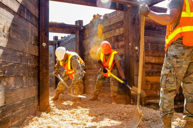 Sgt. Deivy Capellan, left, and Spc. Amade Ouedraogo, both horizontal construction engineers with third platoon, Argonaut Troop, Regimental Engineer Squadron, 2nd Cavalry Regiment, use shovels to level out a bucket full of gravel that had just been dumped in a 100-meter trench on Hohenfels Training Area, Hohenfels, Germany, June 3, 2021. The trench will be utilized for a number of training events throughout the year, beginning with the European Best Sniper Competition Aug. 5-14 on HTA. (U.S. Army photo by Master Sgt. Ryan C. Matson)